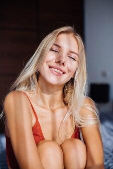 매력적인 귀여운 백인 유럽 여자는 창으로 아름다운 일출 빛을 즐긴다, 그녀는 집에서 침대에있다