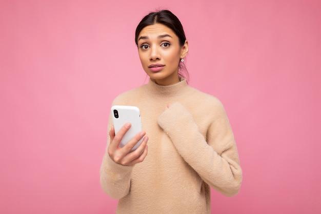 베이지색 따뜻한 스웨터를 입은 매력적인 젊은 브루넷 여성은 분홍색 배경에 고립되어 카메라를 보고 마음에 손을 잡고 전화를 통해 인터넷 서핑을 하고 있습니다.