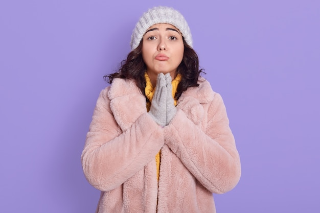 Attractive cute european girl in fur coat, cap and mittens, prays on lilac background, keeping palms together, asking for something important, poses with pout lips.