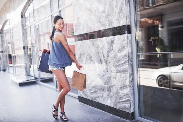 쇼핑에서 즐기는 가방에 매력적인 귀여운 소녀. 모든 여성이 좋아하는 활동