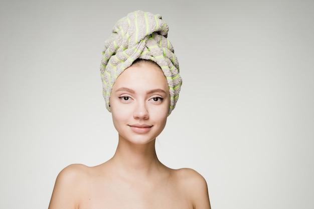 그녀의 머리에 수건으로 매력적인 귀여운 소녀는 아름다워지고 싶어