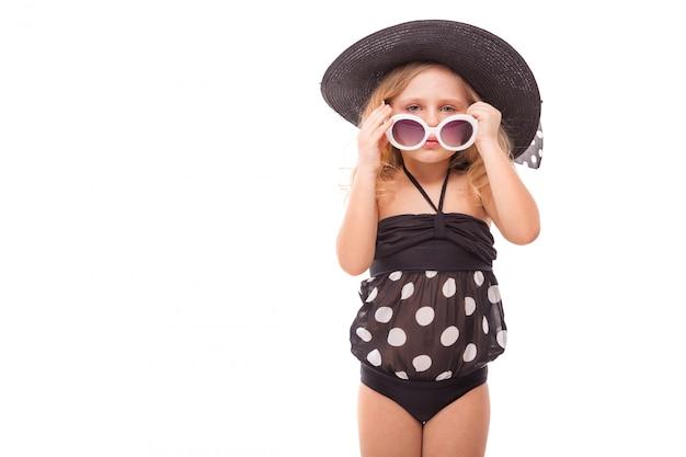 Привлекательная милая маленькая девочка в черном купальнике и черной шляпе держит очки