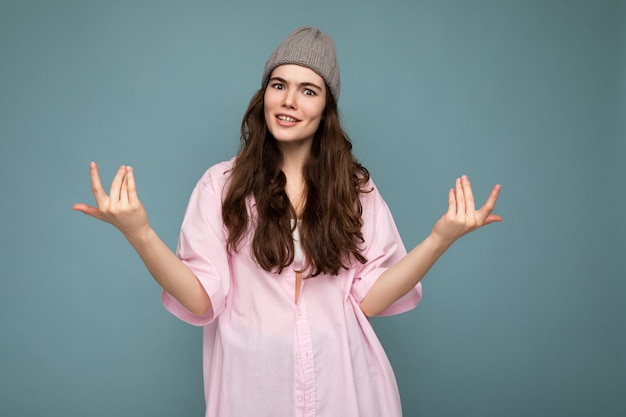 Attractive cute nice adorable tender young curly brunette woman wearing pink shirt and gray hat