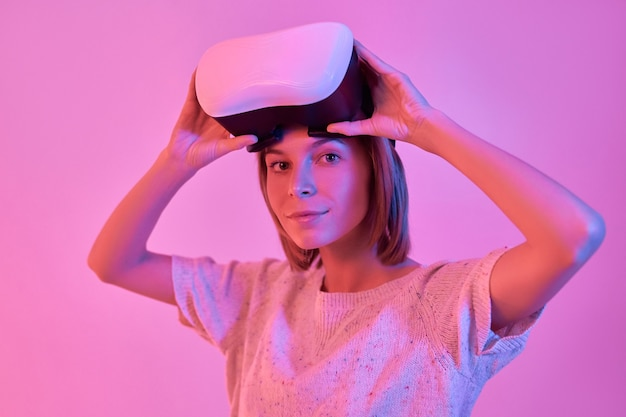 Attractive cute smiling woman in casual wear using virtual reality glasses isolated on neon pink