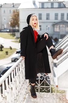 가죽 신발 바지에 세련된 빨간 셔츠에 검은 코트에 빈티지 베레모에 붉은 입술을 가진 매력적인 귀여운 여자 금발은 도시에서 야외에서 쉬고있다