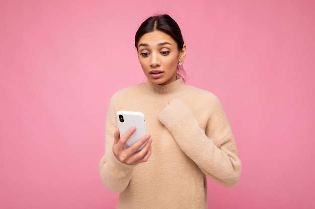 Attractive cute young shocked brunette woman wearing beige warm sweater standing isolated over pink wall surfing on the internet via phone looking at mobile screen and keeping hands on heart.