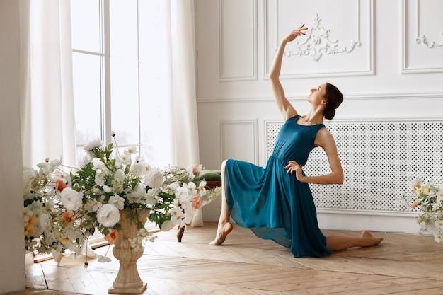 꽃과 빛 스튜디오에서 파란 드레스에 매력적인 댄서
