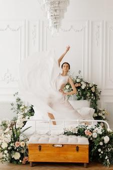 꽃과 함께 침대에 하얀 드레스를 입고 매력적인 댄서