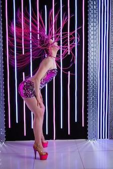 クラブ、ネオンライトでトレンディなピンクのアフロコスを持つ魅力的なダンスの女性。ネオンライトと黒の背景