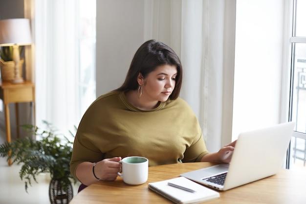Привлекательная темноволосая пухлая женщина-фрилансер сидит в хорошем кафе, проверяет электронную почту и пьет утренний кофе, использует обычный портативный компьютер и держит кружку, смотрит на экран, читает мировые новости