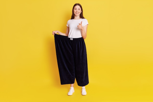 Attractive dark haired female wearing old big trousers after weight lost, has happy, proud expression, pointing index finger to camera, motivates to grow thin, isolated over yellow wall.
