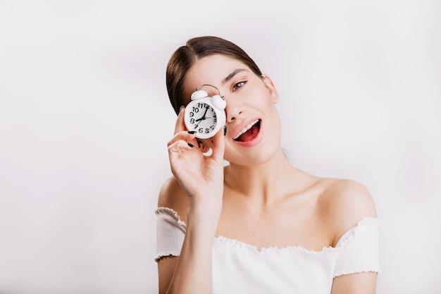 Attraente ragazza dai capelli scuri carino sorride e tiene piccolo orologio, in posa sulla parete isolata.