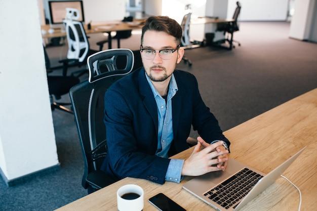 매력적인 검은 머리 남자는 사무실에서 테이블에 앉아있다. 그는 검은 색 재킷에 파란색 셔츠를 입는다. 그는 측면을 찾고 있습니다. 위에서 봅니다.
