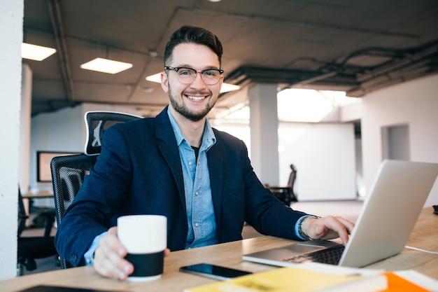 Привлекательный темноволосый мужчина работает за столом в офисе. он носит синюю рубашку с черной курткой. он берет чашку кофе и улыбается в камеру.