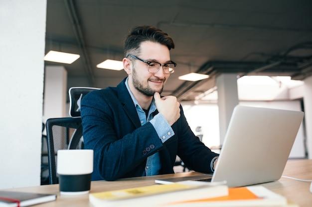 Привлекательный темноволосый мужчина работает с ноутбуком за столом в офисе. он носит синюю рубашку с черной курткой. он улыбается.