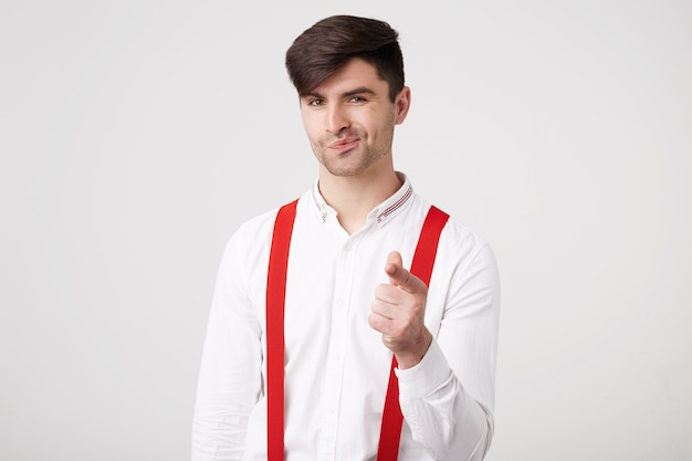 Attractive dark-haired unshaven guy wearing a white shirt and red suspenders shows his index finger