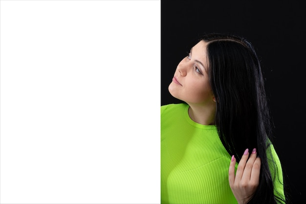 Attractive dark-haired woman in bright colored clothes with a white blank poster, isolated on a dark background