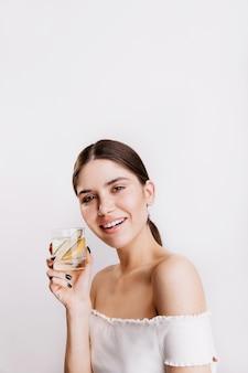 매력적인 검은 머리 여자는 에너지와 미소로 가득 차 있습니다. 레몬 물 잔을 들고 레이디입니다.