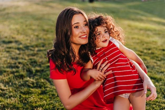Attraente donna dai capelli scuri seduto sull'erba con la figlia. colpo esterno di ridere ragazza riccia che abbraccia la sorellina sulla natura