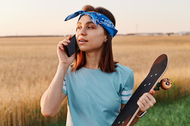 Attractive dark haired woman talking on smartphone with skateboard outdoor in field, waiting friends for skateboarding together, wearing t shirt and hair band.