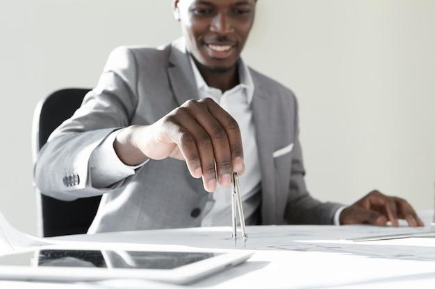 魅力的な浅黒い肌の建築家またはエンジニアで、テクニカルドローイングインストゥルメントを持ち、新しい建築プロジェクトを設計しています。
