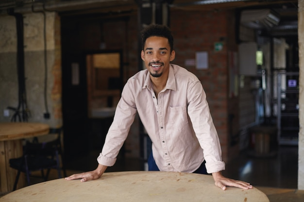 Attractive dark skinned bearded guy with short haircut leaning on round wooden table while looking happily with charming smile, wearing casual clothes over city cafe interior