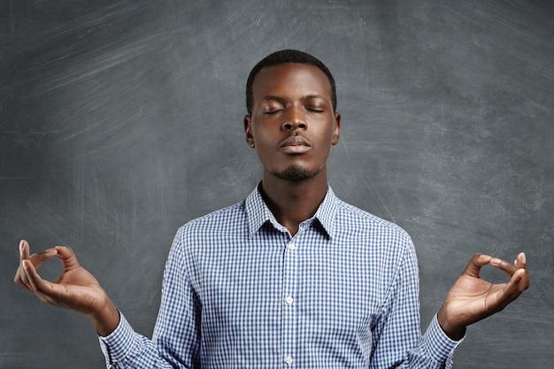 Привлекательный темнокожий бизнесмен с мирным выражением лица медитирует, держась за руки в жесте мудры, держа глаза закрытыми во время практики йоги