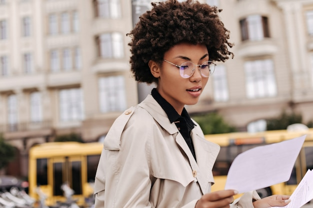 Attractive dark-skinned curly lady in eyeglasses and stylish beige trench coat reads text and holds paper sheet outside