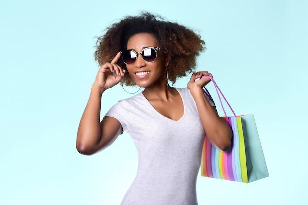 Симпатичная смуглая девушка с белозубой улыбкой и вьющимися волосами держит в руках полосатый бумажный пакет на бледно-голубом фоне.