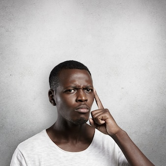 Attractive dark-skinned man wearing white t-shirt holding finger on his temple, trying hard to remember something important, frowning, looking concentrated and focused.