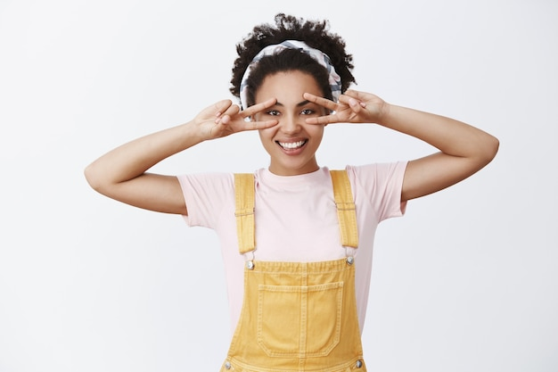 Attractive dark-skinned stylish female woman in headband over hair and yellow trendy overalls, showing peace gesture over eyes and smiling with carefree and happy expression