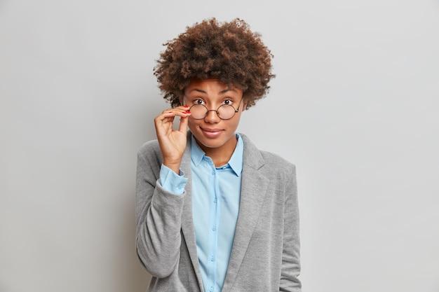 매력적인 어두운 피부를 가진 여자는 안경에 손을 잡고 즐겁게 곱슬 머리를 가지고 있습니다.