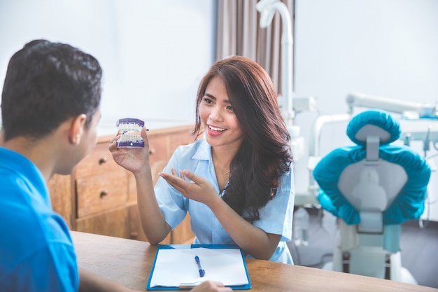 魅力的な歯科医が顎の模型を表示
