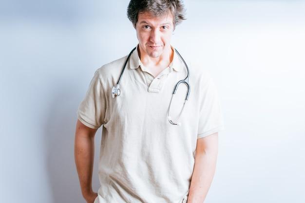 白い背景を持つ彼の首の周りにベージュのポロシャツと聴診器を持つ魅力的な医者の男
