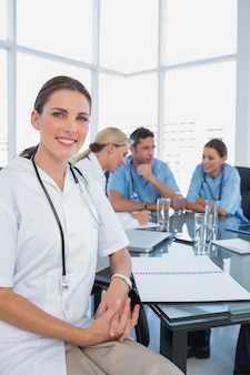 Attractive doctor sitting in front of her team