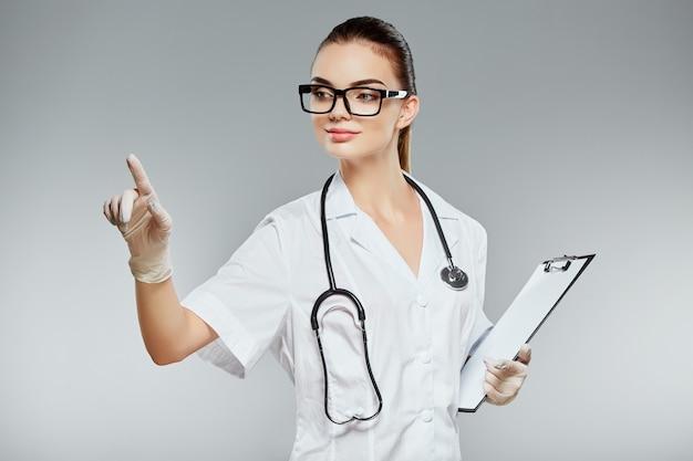Привлекательный доктор с каштановыми волосами и обнаженным телом составляет белую медицинскую форму, очки, стетоскопы и белые перчатки на сером фоне студии и указывая пальцем, держа примечания.
