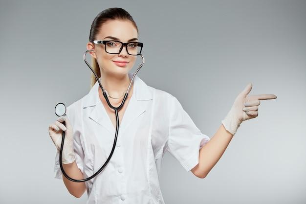 Привлекательный доктор с каштановыми волосами и обнаженным макияжем в белой медицинской форме, очках, стетоскопах и белых перчатках на сером фоне студии и указывая пальцем.