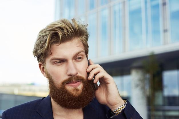 魅力的な疑わしい男が携帯電話で話し、ビジネスビルの近くで屋外を歩きます。スーツを着た真面目な人。