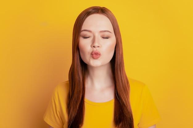 Привлекательная мечтательная женщина отправить воздушный поцелуй на желтом фоне