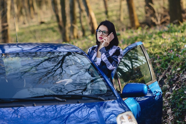 Attractive driver girl looks out of open door of car and talking on phone