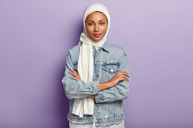 Attractive eastern woman covers head with white headscarf to guard her dignity and power, has special dress code, keeps hands crossed, looks with modesty, poses over purple wall. islamic rules