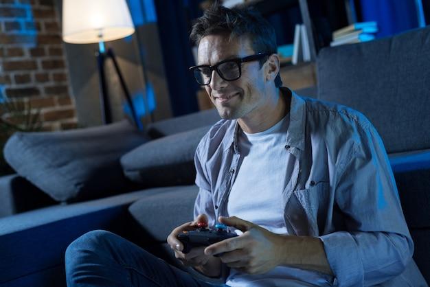 家で夜を過ごし、ビデオゲームをプレイしながら趣味を楽しんでいる魅力的なエキセントリックな焦点を当てた男