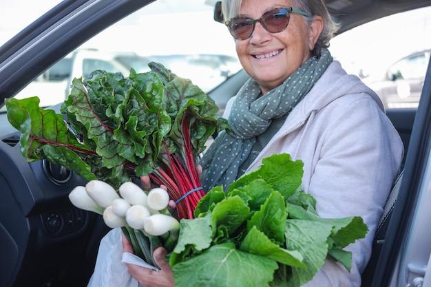 매력적인 할머니는 농민 시장에서 신선한 야채를 사고 차에 탔습니다. 그녀는 그녀의 손에 녹색 양상추와 봄 양파를 들고 있습니다. 건강하고 채식 라이프 스타일 개념