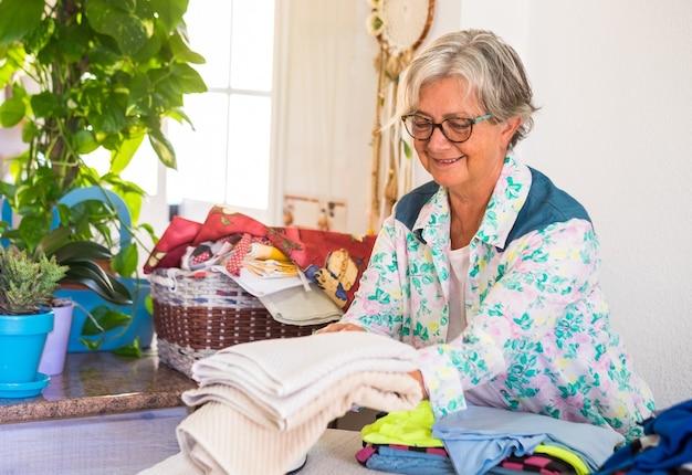 家事で忙しい白髪の魅力的な年配の女性。たくさんの服にアイロンをかける準備ができました。植物と白い壁のある国内の部屋の一角。一人だけ