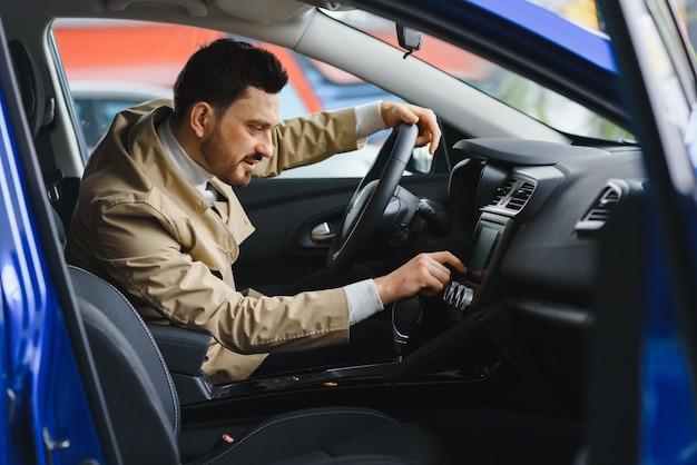 良い車で魅力的なエレガントな幸せな男