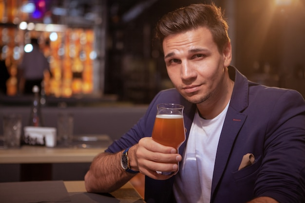 Attractive elegant man smiling to the camera, enjoying tasty beer at the pub