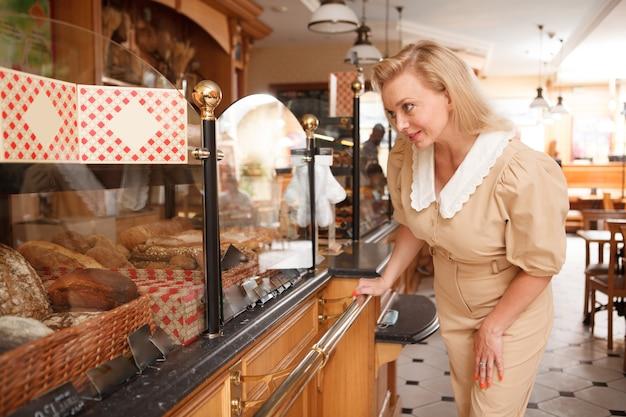 빵집에서 신선한 빵을 사는 매력적인 우아한 성숙한 여성