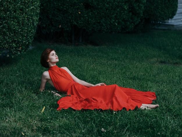 屋外で魅力的なエレガントな女性は草の赤いドレスに横たわっています。高品質の写真