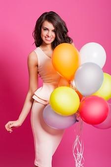 Привлекательная элегантная женщина позирует с воздушными шарами