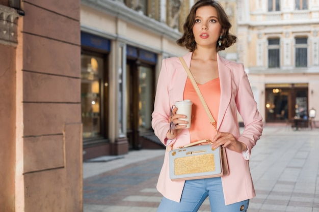 Attractive elegant woman in stylish outfit walking in city, street fashion, spring summer trend, smiling happy mood, wearing pink jacket and blouse, accessories, fashionista on shopping in italy